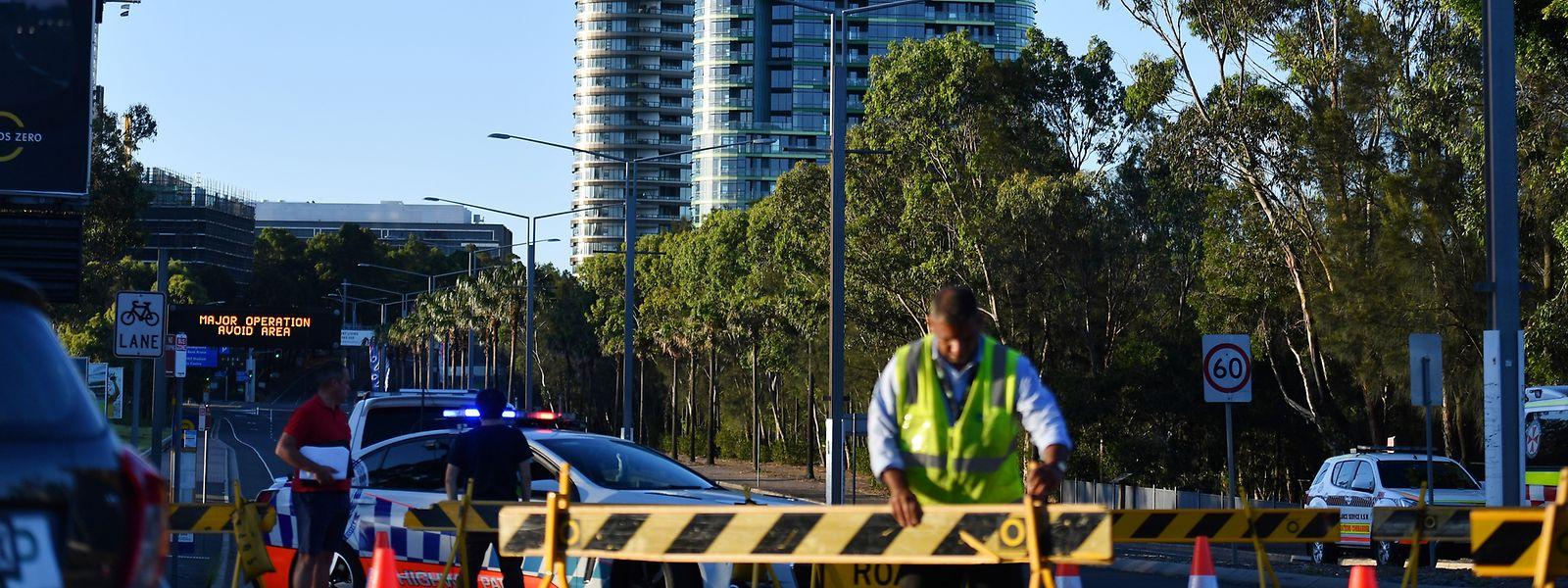 Eine Polizeiabsperrung steht an der Straße zum Hochhaus Opal Tower im Olympiapark. Mehr als 200 Menschen wurden aus einem 36-geschossigen Hochhaus evakuiert, aus Angst, dass das Gebäude einstürzen könnte.