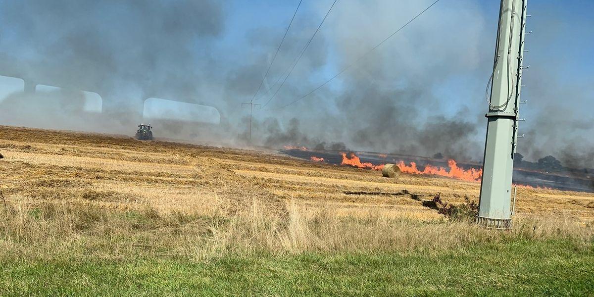 Die Flammen der brennenden Heuballenpresse schlugen schnell auf das Feld über.
