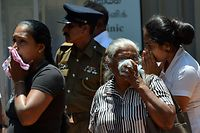 Sri Lankan woman looks into a container where bodies of bomb blast victims are kept at a hospital in Negombo on April 22, 2019, a day after a nearby church was hit in a series of explosions targeting churches and luxury hotels in Sri Lanka. - The death toll from bomb blasts that ripped through churches and luxury hotels in Sri Lanka rose dramatically April 22 to 290 -- including dozens of foreigners -- as police announced new arrests over the country's worst attacks for more than a decade. (Photo by ISHARA S. KODIKARA / AFP)