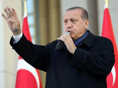 "Turkish president Recep Tayyip Erdogan flashes a four finger sign called ""the rabia sign"" as he delivers a speech to his supporters at the Presidential Palace in Ankara, April 17, 2017"