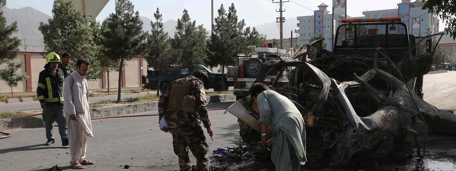 Afghanische Sicherheitskräfte inspizieren am Ort einer Bombenexplosion in Kabul die Überreste eines Fahrzeugs.