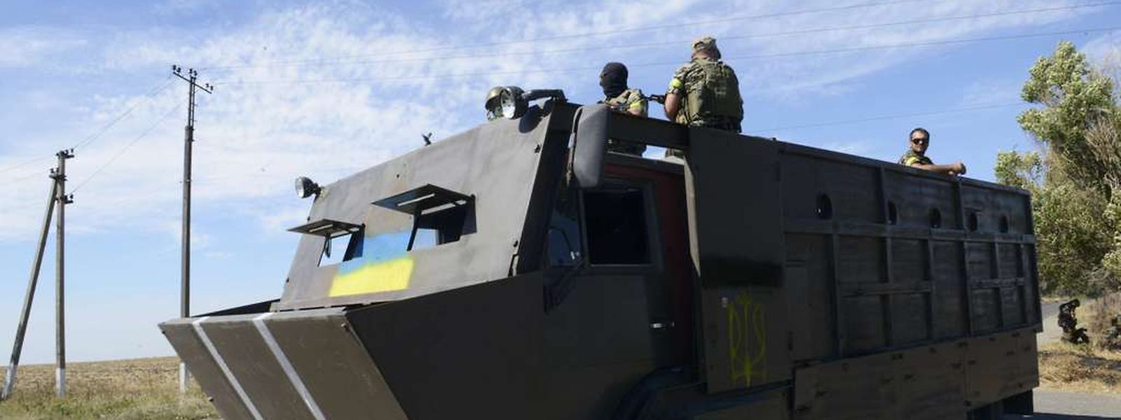 Members of Ukrainian volunteer battalion Dnipro stand in a truck covered in steel plates near the small southern Ukrainian city of Novoazovsk, Donetsk region, on August 27, 2014. Ukraine appealed for NATO's help on August 27 after reporting that a huge convoy of tanks and weaponry from Russia was moving through the southeast of the country. AFP PHOTO/ ALEXANDER KHUDOTEPLY