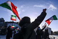 People gesture and wave former flags of Iran as they protest outside the Antwerp criminal court during the trial of four persons including an Iranian diplomate and Belgian-Iranian couple in Antwerp, on February 4, 2021. - A Belgian court returns a verdict on February 4, 2021, in the trial of an Iranian diplomat accused of plotting a bomb attack against opposition activists meeting in France. Assadollah Assadi, a 49-year-old formerly based in Vienna, faces up to 20 years in prison if convicted of plotting to target the June 30, 2018 rally. The gathering in Villepinte outside Paris included senior leaders of the exiled National Council of Resistance in Iran (NCRI) and some high-profile supporters. (Photo by DIRK WAEM / BELGA / AFP) / Belgium OUT