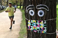"A man jogs past a giant mask and eye display stuck to a tree in Melbourne on May 8, 2020, as Australia's government unveiled a three-stage plan to get the economy back to a new ""COVID-safe"" normal by the end of July. - The first stage of the plan will allow groups of up to 10 people to gather in cafes and restaurants, for weddings and to take part in outdoor sports. (Photo by William WEST / AFP)"