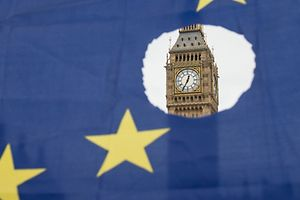 """TOPSHOT - A pro-remain protester holds up an EU flag with one of the stars symbolically cut out in front of the Houses of Parliament shortly after British Prime Minister Theresa May announced to the House of Commons that Article 50 had been triggered in London on March 29, 2017.  Prime Minister Theresa May today said there could be """"no turning back"""" and called for national unity, after notifying the EU of Britain's intention to end its 44-year membership of the bloc. / AFP PHOTO / OLI SCARFF"""