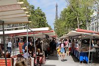 """People wearing face masks walk at a market in front of the Eiffel Tower in Paris, on August 27, 2020, as face masks will become mandatory in the city. - France's prime minister on August 27 announced face masks will become compulsory throughout Paris, expressing concern over an """"undeniable"""" trend of expanding coronavirus infection in the country. Jean Castex said 19 more departments have been added to a map with """"red"""" zones of active virus circulation, meaning 21 of France's 94 departments are classified as such. Official figures released on August 26 showed more than 5,400 confirmed new cases in just 24 hours, with admissions to hospital and intensive care units on the rise. (Photo by Ludovic MARIN / AFP)"""