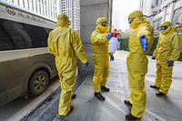 This photo taken on January 30, 2020 shows staff members of a funeral parlour wearing protective suits disinfecting a colleague after they transferred a body at a hospital in Wuhan in China's central Hubei province, during the virus outbreak in the city. - The World Health Organization declared a global emergency over the new coronavirus, as China reported January 31 the death toll had climbed to 213 with nearly 10,000 infections. (Photo by STR / AFP) / China OUT