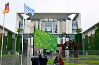 "A demonstrator with the EU flag in green stands in front of  the Chancellery during a protest calling for a ""Green Europe"" on July 1, 2020 in Berlin. - Germany takes over the European Union's six-month presidency, with outgoing Chancellor staking her legacy on a massive economic recovery plan to help the bloc cope with the coronavirus fallout. (Photo by Tobias SCHWARZ / AFP)"