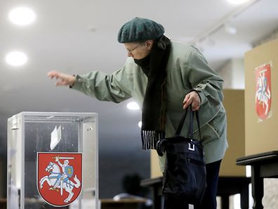 A woman casts her vote during a general election run-off in Birzai, Lithuania, October 23, 2016.