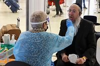 Vaccinated Israelis and tourists get tested for COVID-19 upon arrival to Israel's Ben Gurion airport near Tel Aviv on May 23, 2021, after a partial re-opening of the border to inoculated tourists from 14 countries. (Photo by JACK GUEZ / AFP)