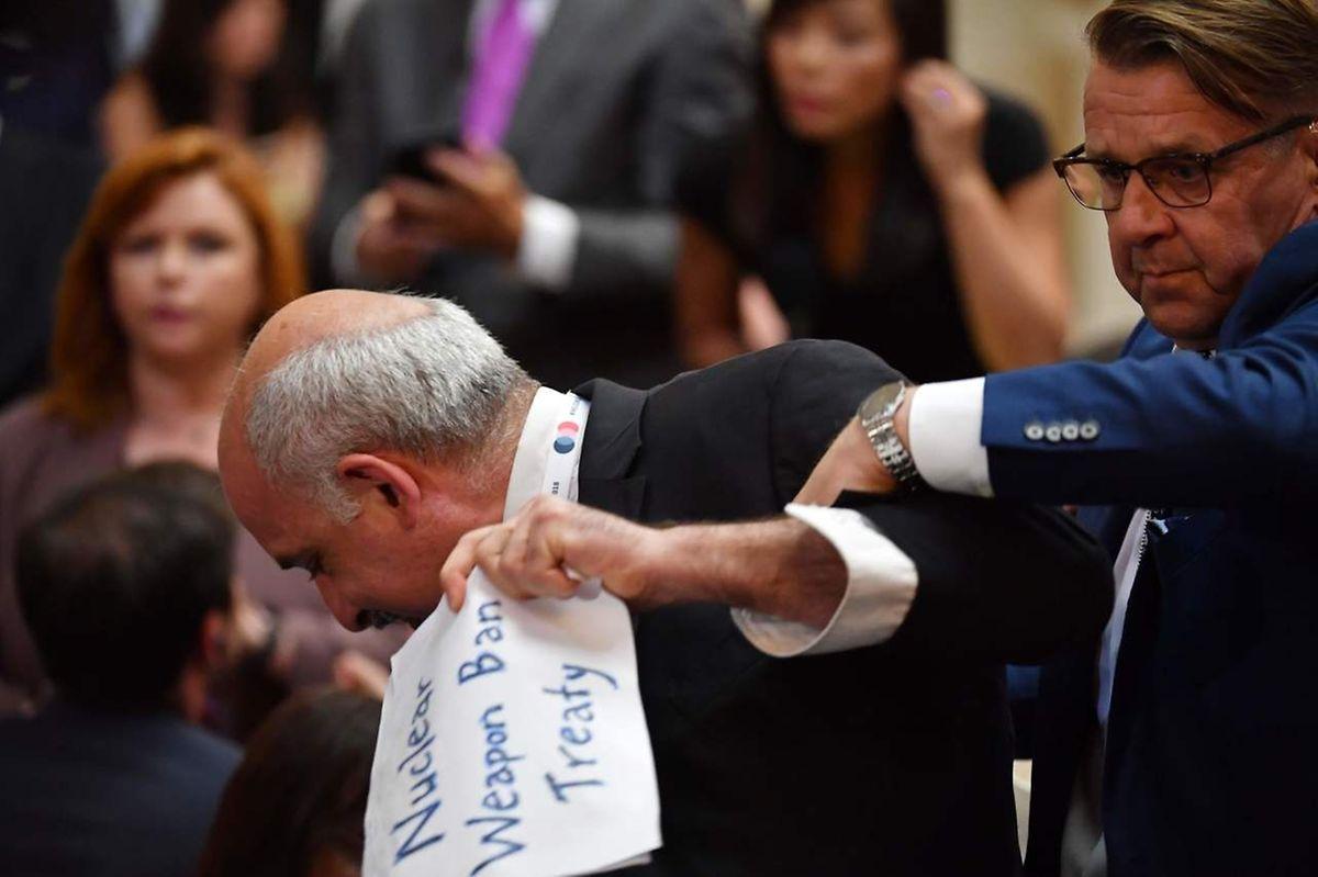 Manifestante foi retirado à força da sala onde ia decorrer a conferência de imprensa de Putin e Trump.