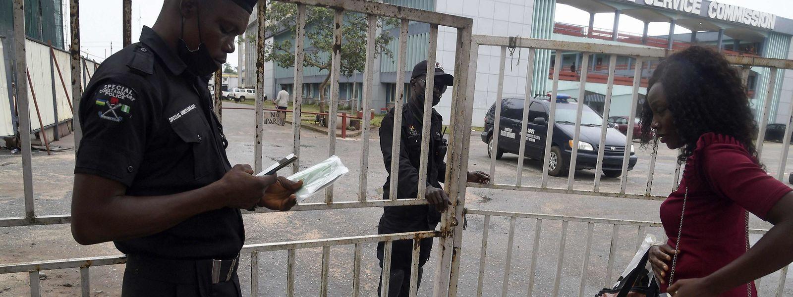 Ein Polizist prüft den Impfausweis einer Büroangestellten im Staatssekretariat in Benin City, der Hauptstadt des Bundesstaates Edo im Süden Nigerias. Dort gilt ein obligatorischer Covid-19-Ausweis für den Zugang zu öffentlichen Plätzen und Versammlungen.