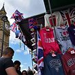 Tourists look at London-themed merchandise as Union flags fly above a street vendor's stall near the Big Ben clock face and the Elizabeth Tower at the Houses of Parliament in central London on June 26, 2016.  Britain's opposition Labour party plunged into turmoil Sunday and the prospect of Scottish independence drew closer, ahead of a showdown with EU leaders over the country's seismic vote to leave the bloc. Two days after Prime Minister David Cameron resigned over his failure to keep Britain in the European Union, Labour leader Jeremy Corbyn faced a revolt by his lawmakers who called for him, too, to quit.  / AFP PHOTO / BEN STANSALL