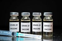An illustration picture shows vials with Covid-19 Vaccine stickers attached, and syringes, on November 17, 2020. (Photo by JUSTIN TALLIS / AFP)