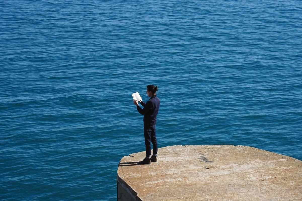 """Fábio Godinho, irmão do artista plástico, lê em silêncio a """"Odisseia"""", de Homero, para depois rasgar as páginas da narrativa fundadora da nostalgia."""