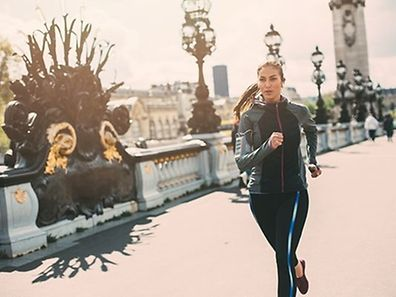 A woman running outside in the  city.