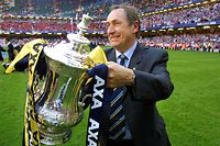 (FILES) In this file photo taken on May 12, 2001 Liverpool's French Manager Gerard Houllier holds the FA Cup trophy after his team beat Arsenal in the final at The Millennium Stadium in Cardiff. - Ex-Liverpool manager Gerard Houllier has died at the age of 73, it was announced on December 14, 2020. (Photo by Adrian DENNIS / AFP)