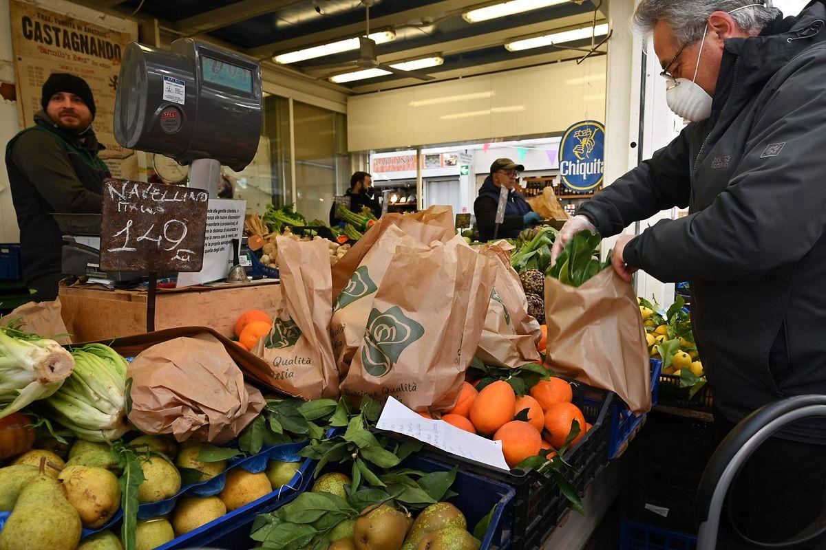 Mit einer Schutzmaske geht ein Kunde auf einem Obst- und Gemüsemarkt in Rom einkaufen.