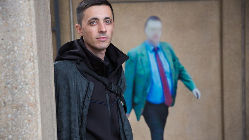 """Paolo Cirio stands in front of one of his 35 """"Street Ghosts"""""""