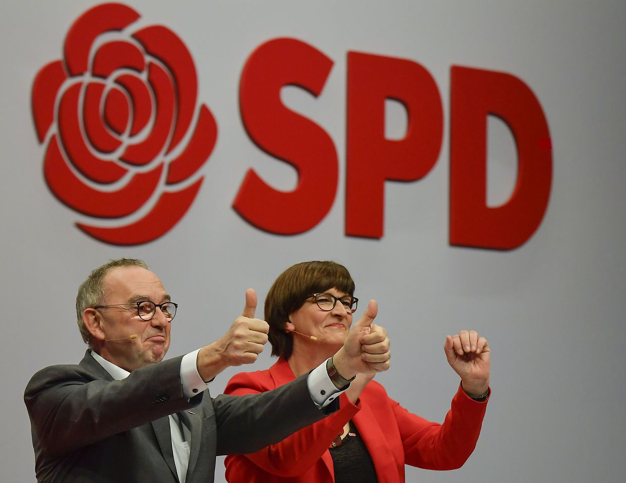 Designated Germany's social democratic SPD party co-leaders Norbert Walter-Borjans and Saskia Esken gesture in front of their party logo during the party congress of Germany's Social Democrats (SPD) at the fairgrounds in Berlin, on December 6, 2019. - Some 600 delegates from the centre-left SPD will be gathering until December 8, 2019 to discuss their next move under a new, more radical leadership. (Photo by Tobias SCHWARZ / AFP)