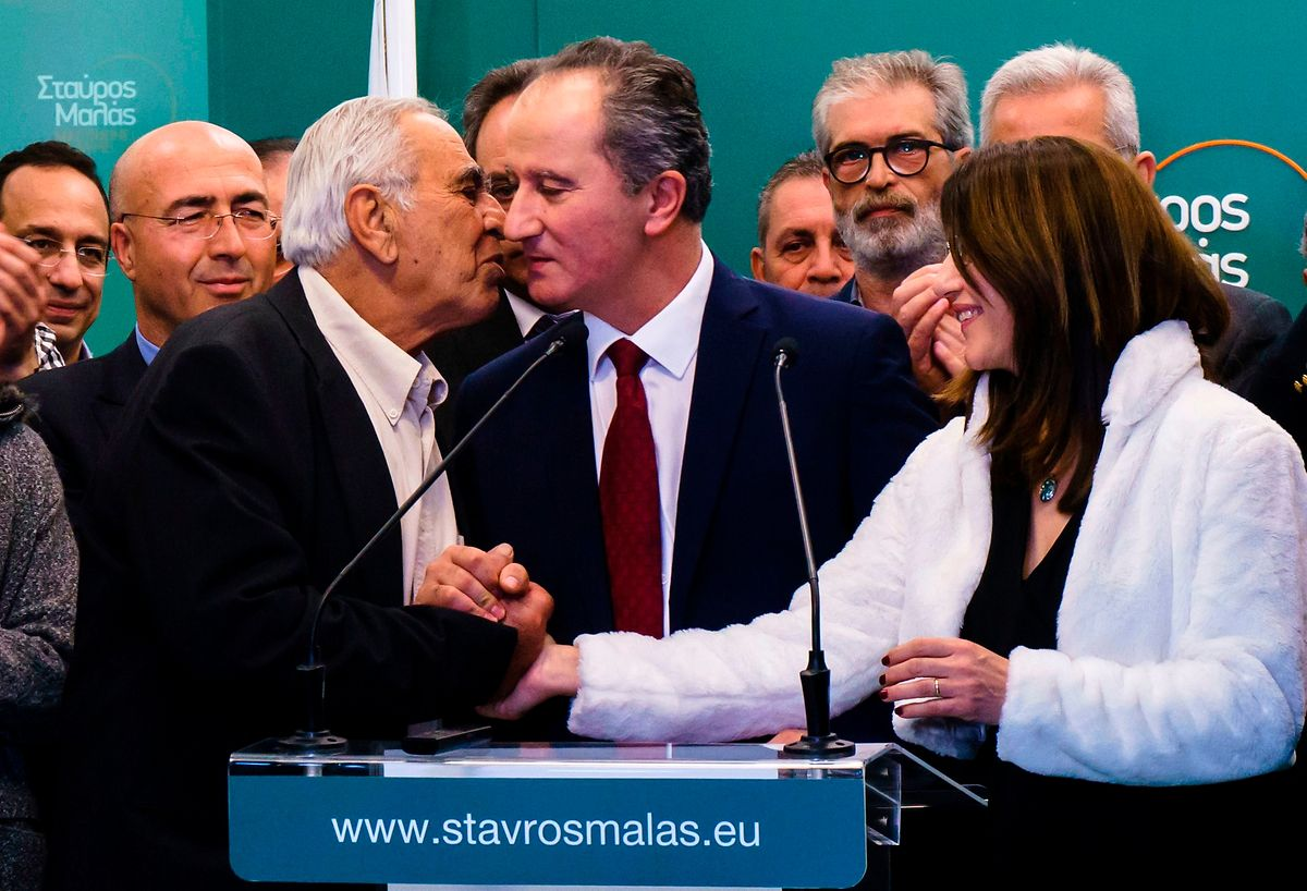 Presidential candidate Stavros Malas (C) kisses his father (L) while his wife Zacharoula (R) holds his hand as he giving a statement to the press after he was defeated in the second round run-off of the Cypriot presidential elections on 4 February 2018 (AFP)