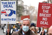 """An Anti-Brexit demonstrator hold placards as EU chief negotiator Michel Barnier (C), wearing a protective face covering to combat the spread of the coronavirus, and members of his team, walks through central London on November 30, 2020 after leaving the conference centre where talks continue on a trade deal between the EU and the UK. - Last-ditch Brexit trade talks continued in London with fishing rights remaining an """"outstanding major bone of contention,"""" according to British foreign minister Dominic Raab. (Photo by DANIEL LEAL-OLIVAS / AFP)"""