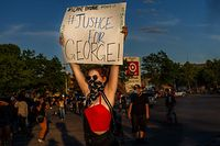 "TOPSHOT - A protester hold sign board ""Justice for George"" into a fire outside a Target store near the Third Police Precinct on May 28, 2020 in Minneapolis, Minnesota, during a demonstration over the death of George Floyd - A police precinct in Minnesota went up in flames late on May 28 in a third day of demonstrations as the so-called Twin Cities of Minneapolis and St. Paul seethed over the shocking police killing of Floyd. The precinct, which police had abandoned, burned after a group of protesters pushed through barriers around the building, breaking windows and chanting slogans. A much larger crowd demonstrated as the building went up in flames. (Photo by Kerem Yucel / AFP)"