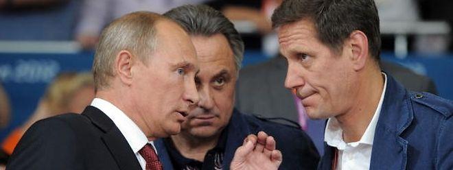 Vladimir Putin com Vitaly Mutko, ministro russo do Desporto, e Alexander Zhukov, presidente do Comité Olímpico.