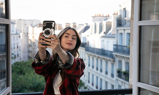 Emily, played by Lily Collins takes a selfie out of the window of her Paris apartment