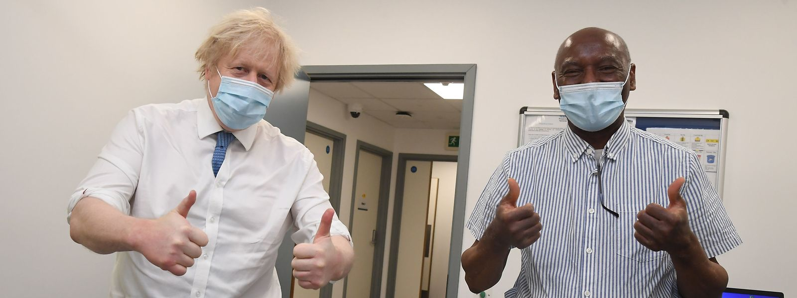Der britische Premier Boris Johnson und Impfkandidat Silvester Biyibi (r.) posieren im Impfzentrum in Orpington im Südosten Londons.