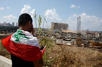 TOPSHOT - A man draped in a Lebanese flag reacts as he stands before the ravaged port of Lebanon's capital Beirut on August 9, 2020, in the aftermath of a colossal explosion that occurred days prior due to a huge pile of ammonium nitrate that had languished for years at a port warehouse. - The huge chemical explosion that hit Beirut's port, devastating large parts of the Lebanese capital and claiming over 150 lives, left a 43-metre (141 foot) deep crater, a security official said. The blast Tuesday, which was felt across the country and as far as the island of Cyprus, was recorded by the sensors of the American Institute of Geophysics (USGS) as having the power of a magnitude 3.3 earthquake. (Photo by PATRICK BAZ / AFP)