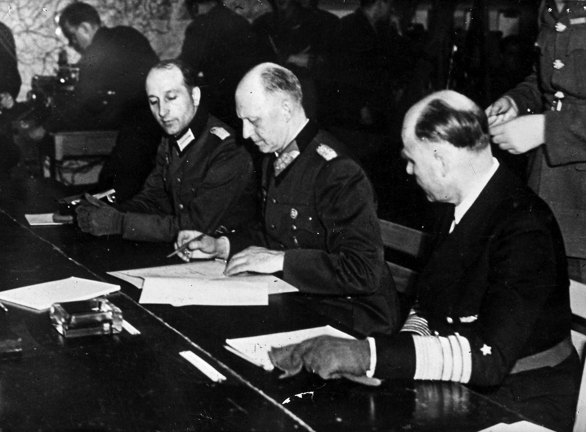 Am 7. Mai 1945 unterzeichnen General Jodl (Mitte) und Admiral Friedeburg (rechts) die bedingungslose Kapitulation in Reims, die am 8. Mai in Kraft tritt. Auf Drängen der Sowjets wird diese Zeremonie zwei Tage später wiederholt.