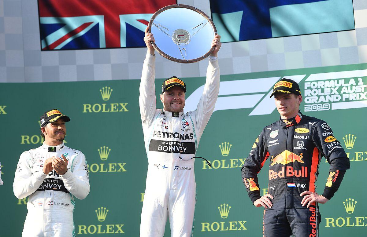Mercedes-Pilot Valterri Bottas (M) aus Finnland hält die Siegertrophäe auf dem Podium. Links der Zweitplatzierte Lewis Hamilton aus Großbritannien (Mercedes). Rechts Red Bull-Fahrer Max Verstappen aus den Niederlanden, der Dritter wurde.