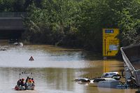 """TOPSHOT - A rescue boat patrols next to submerged vehicles on the federal highway B265 in Erftstadt, western Germany, on July 17, 2021. - Devastating floods in Germany and other parts of western Europe have been described as a """"catastrophe"""", a """"war zone"""" and """"unprecedented"""", with more than 150 people dead and the toll still climbing on July 17, 2021 (Photo by SEBASTIEN BOZON / AFP)"""