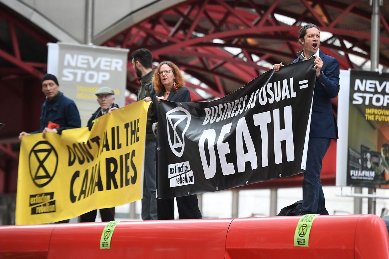 Elementos do Extinction Rebellion manifestam-se no topo de um comboio em Londres.