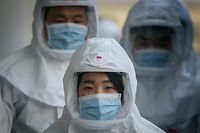 TOPSHOT - In this photo taken on March 12, 2020, medical workers wearing protective clothing against the COVID-19 novel coronavirus walk to a decontamination area at the Keimyung University hospital in Daegu. - South Korea -- once the largest coronavirus outbreak outside China -- saw its newly recovered patients exceed fresh infections for the first time on March 13, as it reported its lowest number of new cases for three weeks. (Photo by Ed JONES / AFP)