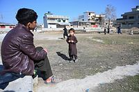 """In this picture taken on February 11, 2021, children play cricket at the site of the demolished compound of slain former Al-Qaeda leader Osama bin Laden, in northern Abbottabad. - Children play cricket in a patch of scorched grass and scattered rubble in Abbottabad -- all that remains of the final lair of the most wanted person on the planet. It was in this Pakistani city that Osama bin Laden was killed in the clandestine """"Operation Geronimo"""" raid by US Navy Seals in the early hours of May 2, 2011. (Photo by Farooq NAEEM / AFP) / TO GO WITH 'US-Pakistan-BinLaden-Anniversary-Abbottabad'"""