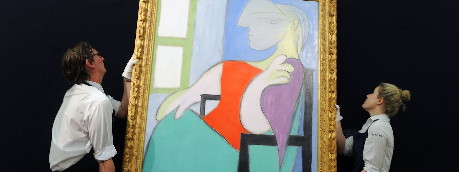 Mitglieder des Auktionshauses Sotheby's hängen das Gemälde von Pablo Picasso auf.