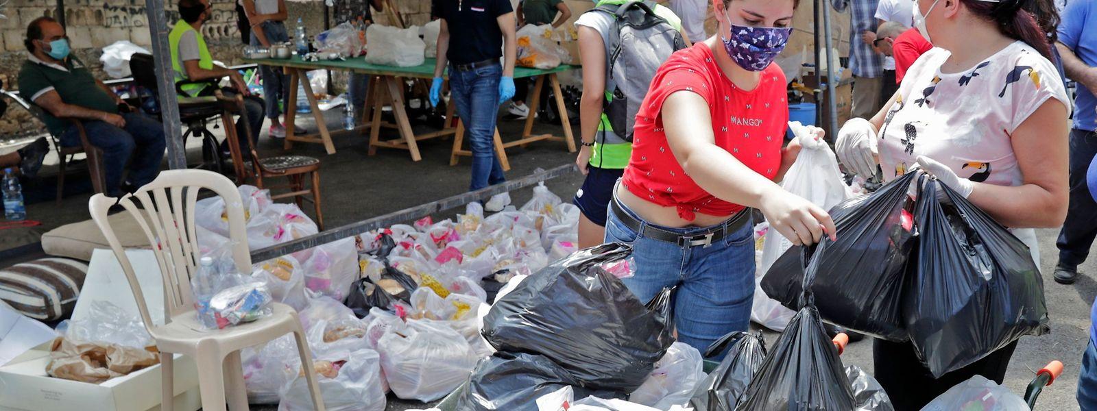 Freiwillige Helfer verteilen in Beirut Lebensmittel.