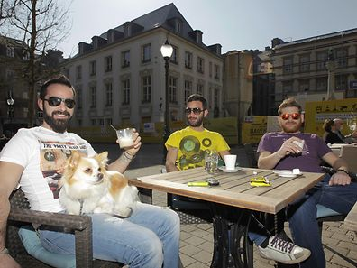 Three men and their dog enjoying a drink in the sunshine on Place d'Armes.