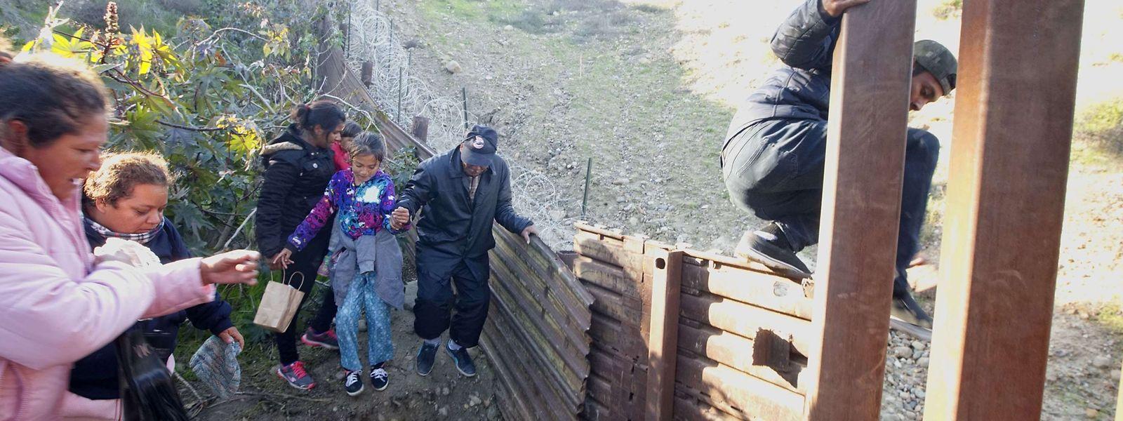 Des migrants en provenance du Honduras escaladent la barrière à la frontière entre le Mexique et les Etats-Unis.