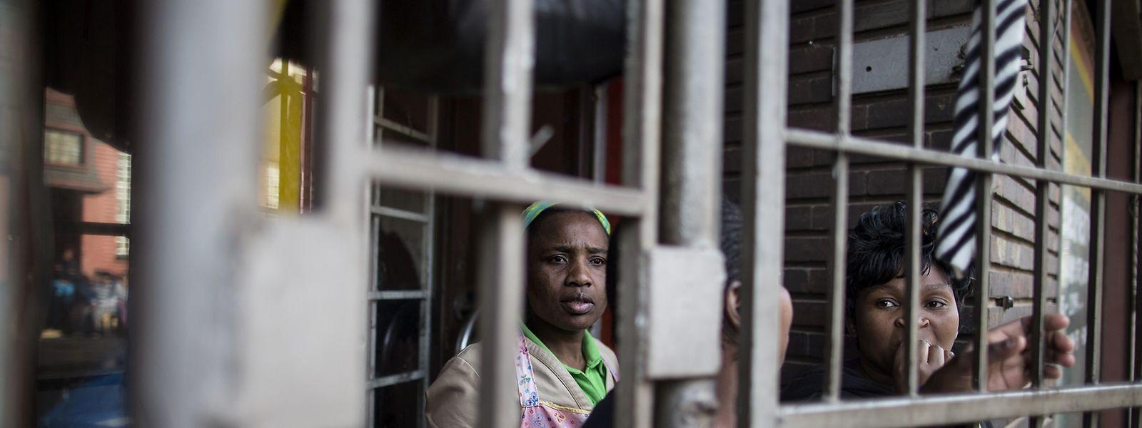 Geschützt hinter den Gittern beobachten ausländische südafrikanische Frauen, wie eine Menge von aufgebrachten Zulu, vor dem Hospiz im Stadtteil Jeppestown in Johannesburgs, gegen sie protestiert.