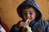 A migrant child eats bread inside an abandoned building in Edirne, northwestern Turkey on March 6, 2020. - The EU is preparing an additional 500 million euros in aid for Syrian refugees in Turkey to ease tensions with Ankara, European sources told AFP on Thursday. (Photo by Ozan KOSE / AFP)