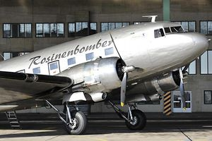 """A vintage Douglas DC-3 aircraft, known as a """"Rosinenbomber"""" (candybomber) waits to take on passengers for a flight over Berlin at Tempelhof airport, on October 23, 2008. The aircraft, which served under the RAF during the 1948-49 Berlin airlift, will be flying out of Schoenefled starting November 2008, as Tempelhof will close at the end of October 2008. AFP PHOTO JOHN MACDOUGALL"""
