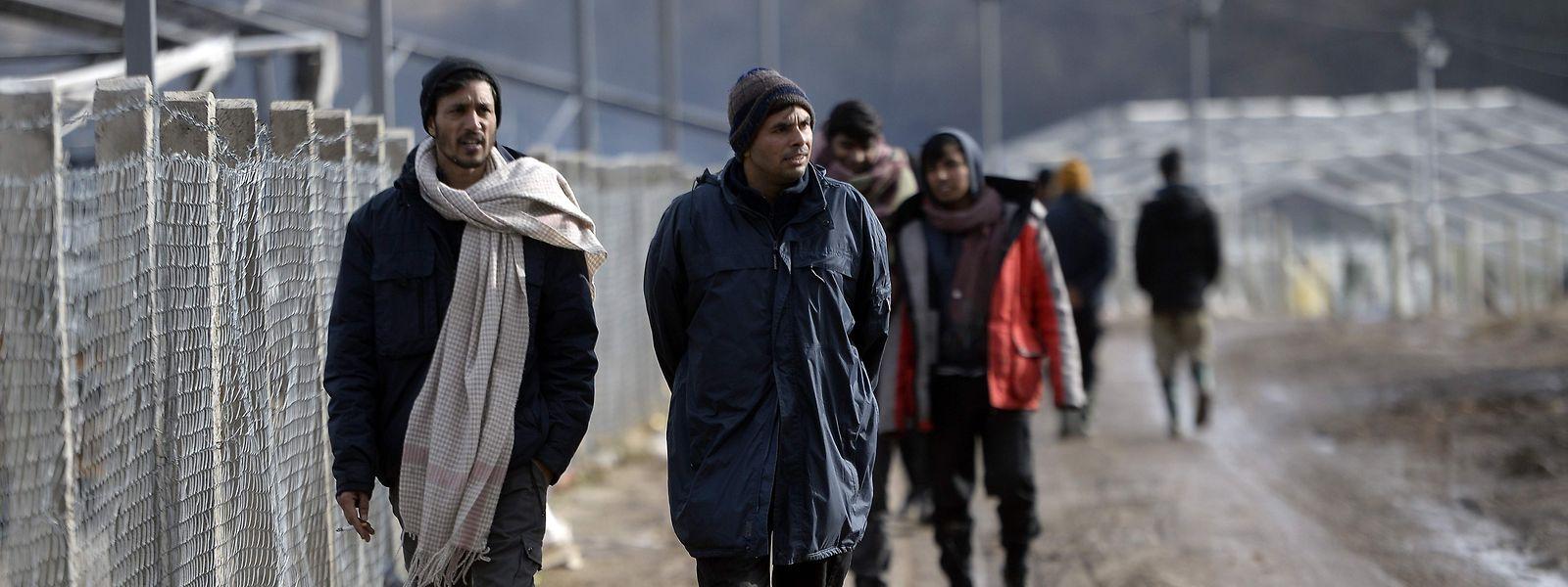 Geflüchtete gehen am Zaun des Lagers Lipa unweit der bosnischen Stadt Bihac entlang.