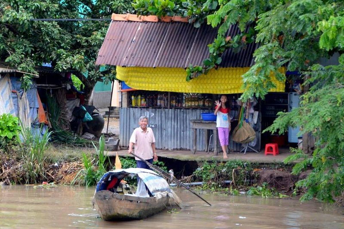 Sur le canal de Chao Gao, les pêcheurs qui vivent au bord de l'eau nous font des signes et des sourires