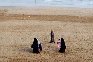 (FILES) This file photo taken on August 12, 2016 shows Moroccan women wearing the niqab, walking on the beach with their children in Casablanca. The debate launched this summer in France over the Burkini is not causing such a stir in North Africa where the Islamic swimsuit is uncontroversial as the dress-code on the beaches has become increasingly prudish.  / AFP PHOTO / Emily IRVING-SWIFT / TO GO WITH AFP STORY BY AMAL BELLALOUFI WITH AFP CORRESPONDENTS IN RABAT AND TUNIS