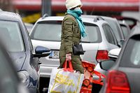 13.03.2020, Austria, Salzburg: A woman with a face mask carries her purchases over the parking lot of a shopping center. In the fight against the corona virus, many shops in Austria will have to close temporarily next week. Food markets and pharmacies can remain open, said Federal Chancellor Kurz on Friday in Vienna. Photo: Barbara Gindl / APA / dpa +++ dpa-Bildfunk +++