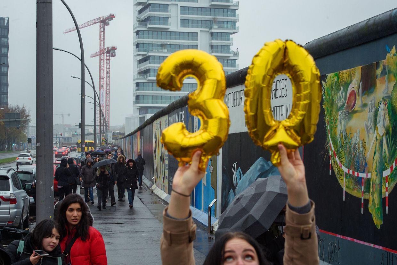 09.11.2019, Berlin: Eine Besucherin hält vor der East Side Gallery, der ehemaligen Berliner Mauer, Luftballons in Form einer goldenen «30» in die Höhe. Foto: Gregor Fischer/dpa +++ dpa-Bildfunk +++