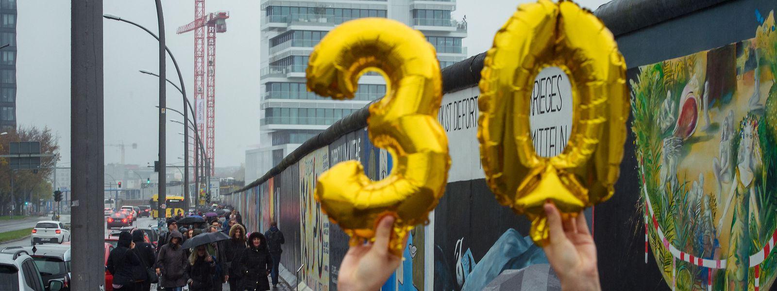 Eine Besucherin hält vor der East Side Gallery, der ehemaligen Berliner Mauer, Luftballons in Form einer goldenen «30» in die Höhe.
